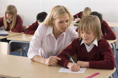 Teacher helping school boy with test in classroom Royalty Free Stock Image