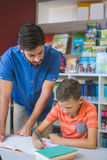 Teacher helping school kid with his homework in library Stock Images
