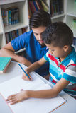 Teacher helping school kid with his homework in library Royalty Free Stock Photos