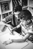 Teacher helping school kid with his homework in library royalty free stock photo