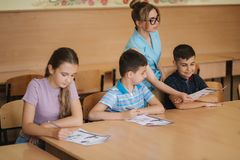 Teacher helping school kids writing test in classroom. education, elementary school, learning and people concept.  stock photo