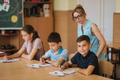 Teacher helping school kids writing test in classroom. education, elementary school, learning and people concept.  royalty free stock photo