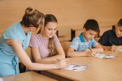 Teacher helping school kids writing test in classroom. education, elementary school, learning and people concept.  stock image