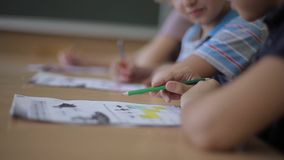 Teacher helping school kids writing test in classroom. education, elementary school, learning and people concept.  stock footage
