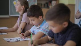 Teacher helping school kids writing test in classroom. education, elementary school, learning and people concept stock video
