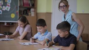 Teacher helping school kids writing test in classroom. education, elementary school, learning and people concept.  stock video footage