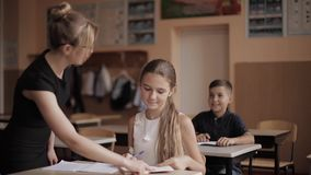 Teacher helping school kids writing test in classroom. education, elementary school, learning and people concept stock video footage