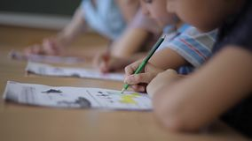 Teacher helping school kids writing test in classroom. education, elementary school, learning and people concept stock footage