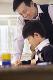 Teacher helping schoolboy with arts and crafts, Beijing Stock Photography