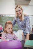 Teacher helping schoolgirl with her homework in classroom Royalty Free Stock Photo