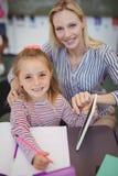 Teacher helping schoolgirl with her homework in classroom Royalty Free Stock Images