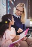 Teacher helping schoolgirl with her homework in classroom Stock Photo