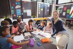 Teacher helping schoolgirl with her homework in classroom Royalty Free Stock Image