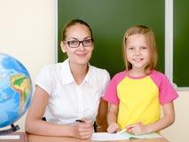 Teacher helping schoolgirl with schoolwork in classroom Royalty Free Stock Images