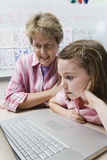 Teacher Helping Schoolgirl Use Laptop Royalty Free Stock Photo
