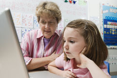 Teacher Helping Schoolgirl Use Laptop Stock Photo