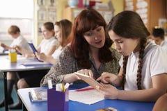 Teacher helping schoolgirl using a tablet computer in class Stock Photo