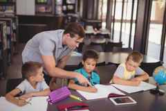 Teacher helping schoolkids with their homework in library. At school Stock Photography
