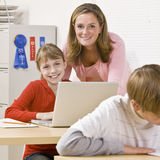 Teacher helping student. Student and her teacher smile at the camera while working at a laptop in class Stock Photo
