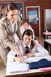 Teacher helping student. High school teacher helping student in classroom Stock Images