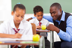 Teacher helping student. Elementary school teacher helping student in classroom royalty free stock photography