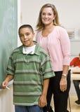 Teacher helping student at blackboard Royalty Free Stock Photos
