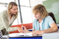 Teacher helping student in class Stock Photo