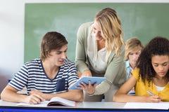 Teacher helping student in class. Female teacher helping student in her class Royalty Free Stock Photo