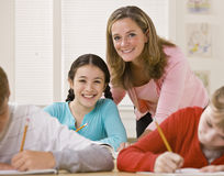 Teacher helping student in classroom Royalty Free Stock Photos