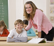 Teacher helping student in classroom Royalty Free Stock Image