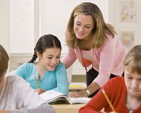 Teacher helping student in classroom Stock Image
