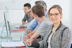 Teacher helping it student at classroom Stock Photography