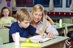 Teacher helping student in classroom Royalty Free Stock Photo