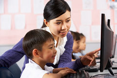 Teacher Helping Student During Computer Class Stock Photos
