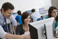 Teacher Helping Student In Computer Lab. High school teacher helping student in computer lab stock image