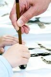Teacher Helping Student drawing hieroglyph. Japan Royalty Free Stock Photo
