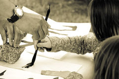 Teacher Helping Student drawing hieroglyph. Japan Stock Photos
