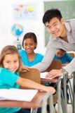 Teacher helping student. Handsome elementary school teacher helping student in classroom Royalty Free Stock Photo