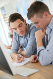Teacher helping student during the informatics class Royalty Free Stock Images