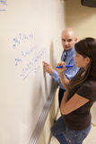Teacher helping student with a math problem on a whiteboard. Bald teacher helping female student with a math problem on a whiteboard Stock Photography