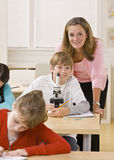 Teacher helping student with microscope Stock Image