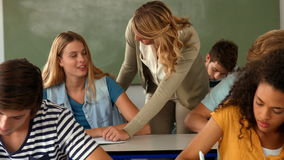 Teacher helping student with paper stock footage