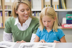 Teacher helping student with reading skills. Kindergarten teacher helping student with reading skills