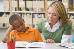 Teacher helping student with reading skills. Kindergarten teacher helping student with reading skills royalty free stock photography