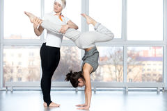 Teacher helping student to do stag handstand. Fitness practice, instructor helping young beautiful student female to do handstand pose with bent legs in class Royalty Free Stock Photo