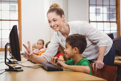 Teacher helping a student using a computer Stock Photo