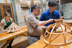 Teacher helping a student in a woodwork class. Student and teacher standing in a woodwork class and working on a structure stock image