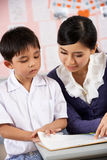 Teacher Helping Student Working At Desk Royalty Free Stock Photography
