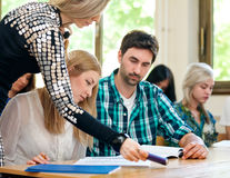 Teacher helping students. With assignment Stock Images