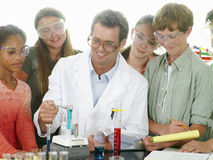 Teacher helping students (12-14) with chemistry experiment Royalty Free Stock Images